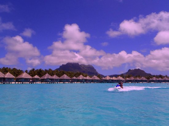 The St. Regis Bora Bora Resort: view of bunglows and mountain from water