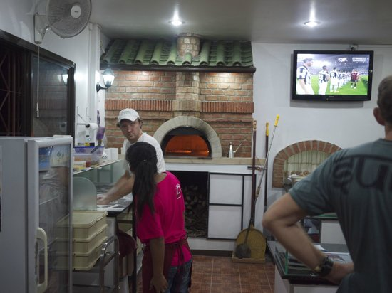 Pizzeria AGLI AMICI da Michele & Jimmy: Looking at the pizza oven and the chef in action