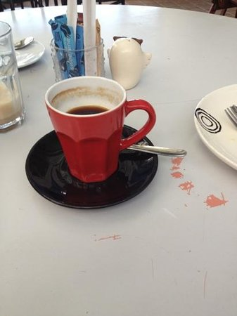The Busy Baker & Cafe: a very long long black and a scratched table and past its best plate.