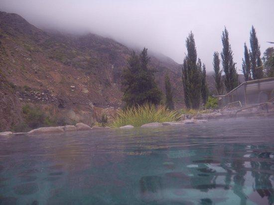 Hotel & Spa Termas Cacheuta: Vista a las montañas que estánfrente al complejo, desde una pileta terma en día de lluvia
