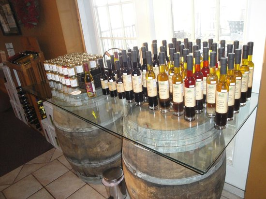 Spicewood Vineyards: Barrels and glass table filled with various flavors of olive oils for purchase