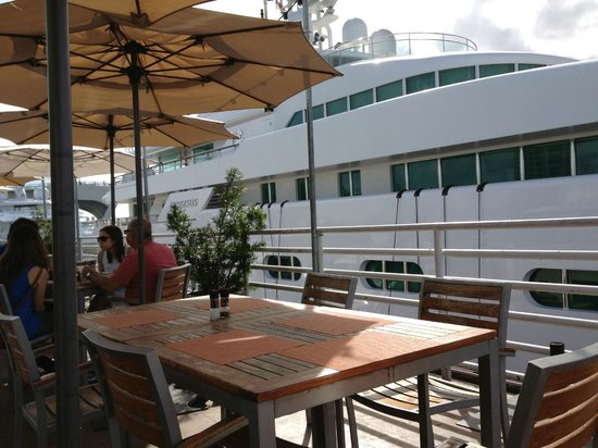 Pelican Landing Restaurant: Shaded Tables looking out on Huge Yachts Docked