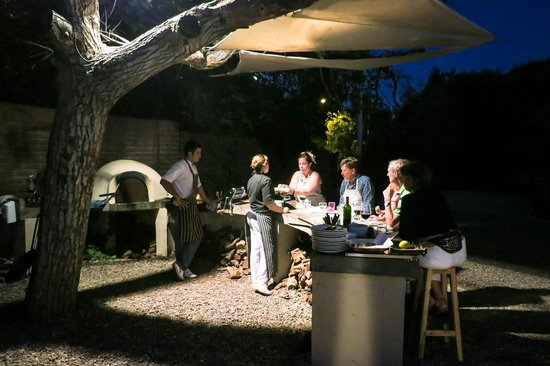 Cooking Class by Cristina Brino :                                     Sitting under the tree by the asado