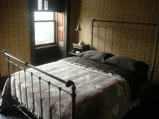 The Harlem Flophouse: Reproduction cast iron bed.