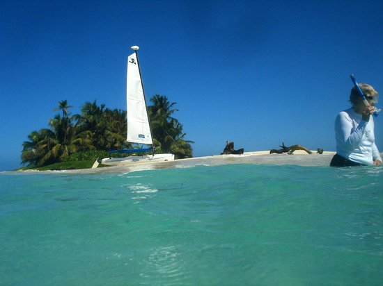 Hatchet Caye Resort:                   Sailboat and snorkeler at Silk Cayes