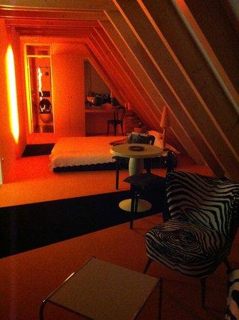 Arthotel Billie Strauss: großes Zimmer mit Kochnische, kleinem Bad und Balkon im orangen Stockwerk
