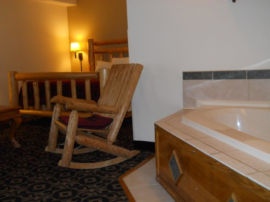 Quality Inn & Suites University:                   Entering the room with whirlpool to right and large bed and couch near.