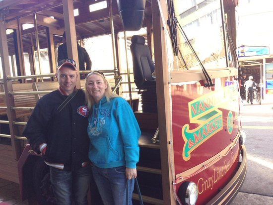 The San Francisco Sightseeing Company: standing in front of the trolley at the pick up point.