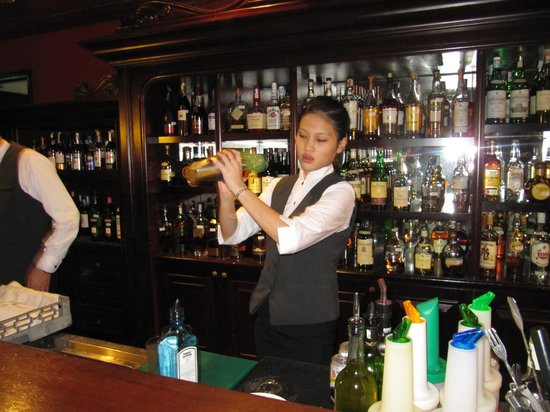 Eastern & Oriental Hotel:                   The delightful cocktail waitress making an E&O sling.