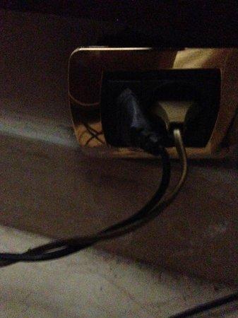 Triumph Hotel :                   Plug hanging off wall