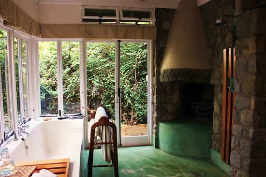 Gibb's Farm: The indoor shower, fireplace and outdoor shower in background