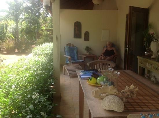 Villa L'Orangerie:                   het priveterras van het appartement met uitzicht op de tropische tuin en vogel