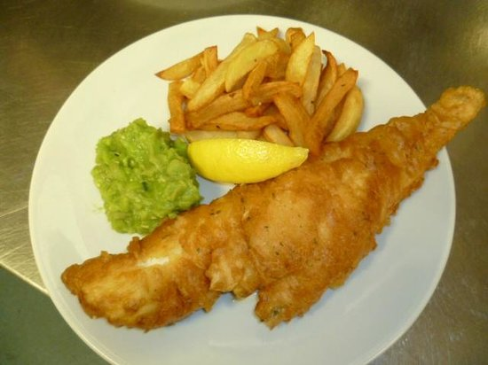 Gilcrux, UK: Our very popular Jennings beer battered haddock, chips and homemade mushy peas