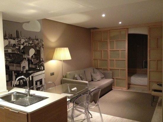 Eric Vokel Boutique Apartments - Gran Via Suites: Soggiorno visto dalla cucina con stanza balcone in fondo