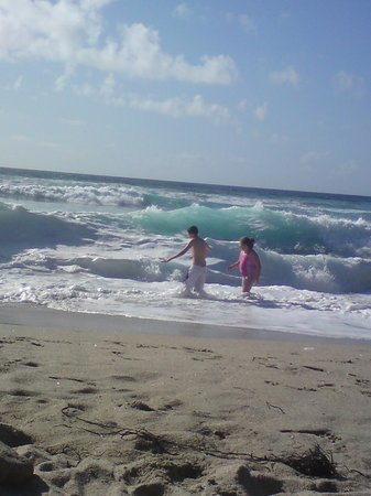 Trevedra Farm Caravan and Camping Site: Kids play in smaller surf waves at Gwenver Beach overlooked by Lifeguards