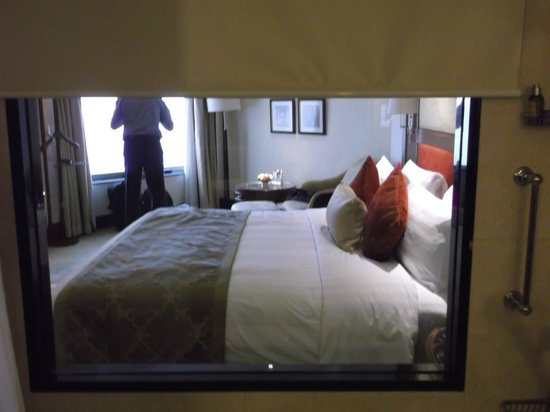 Shangri-La's Eros Hotel: view from bathroom into bedroom -blind can be lowered