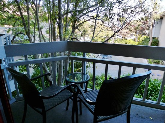 BEST WESTERN PLUS Victorian Inn:                   Our balcony with a little peek of the Pacific through the trees.