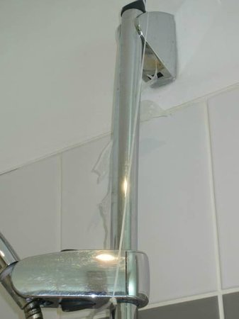 Short Stay Apartment Museum View :                                     Shower head being held up by a plastic quick fix