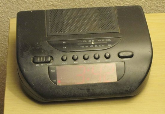 Riverwalk Inn & Suites:                   Old beat-up clock radio, alarm doesn't work either.