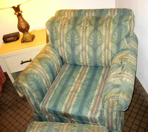 Riverwalk Inn & Suites:                   Old stained & worn out comfy chair & hassock.