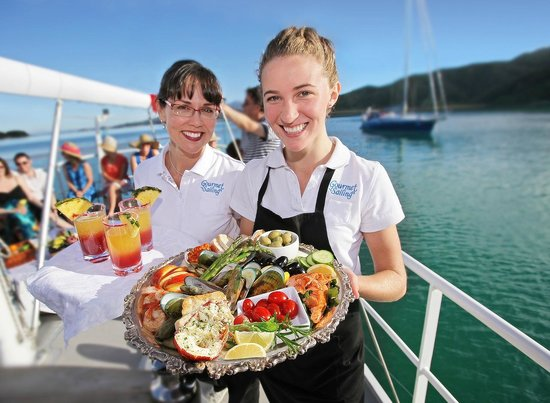 Gourmet Sailing stewardesses serve drinks and platter