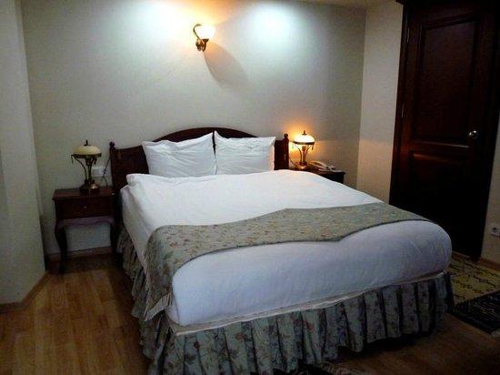 Basileus Hotel: cama doble con mesitas habitación primer piso