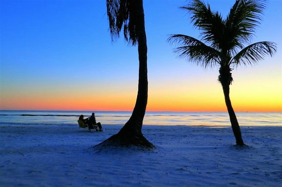Tiki On The Beach:                   couple watching sunset on beach