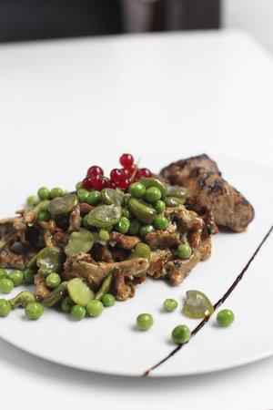 Delikatesy Esencja: Pork loins with chanterelles, broad bean and green peas.