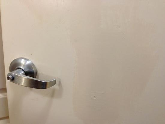 Hilton Garden Inn Tallahassee Central :                   Dirty bathroom door with mismatched paint.