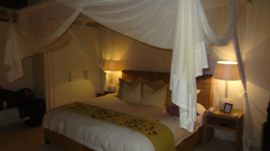 Lion Sands River Lodge: HUGE king bed with welcome flowers!