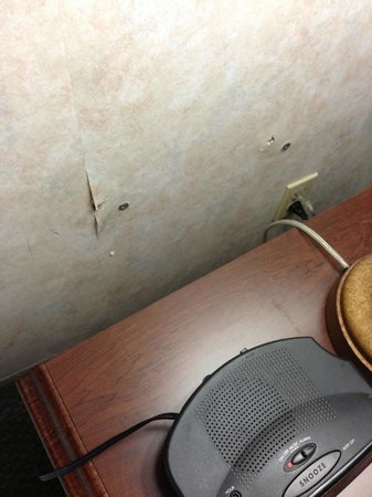 University Square Hotel: Don't know whats going on here... nightstand pulled away from wall and holes
