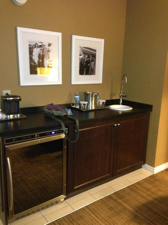 Hilton St. Louis Airport:                                     large bar area with huge refrigerator and wet bar area and a