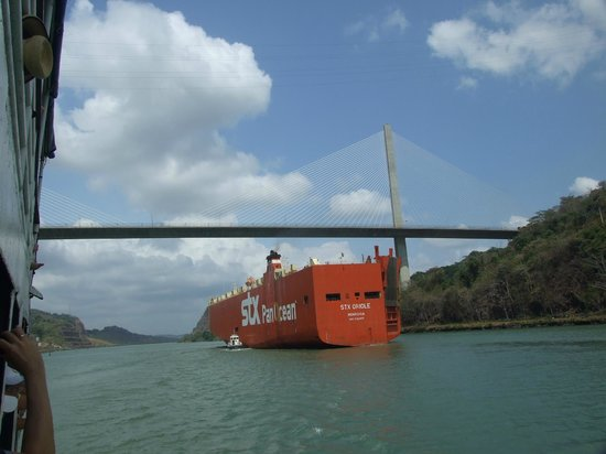 Canal de Panamá:                   A cargo ship going under the bridge linking one side of the canal to the other