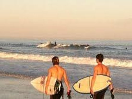 Sandpeddler Inn & Suites: Surfers in the setting sun at Wrightsville Beach