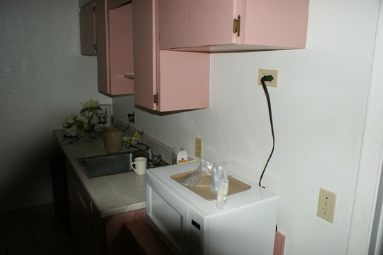 Days Inn & Suites by Wyndham Port Richey:                   Kitchenette area. That cord goes to the microwave sitting on the counter.