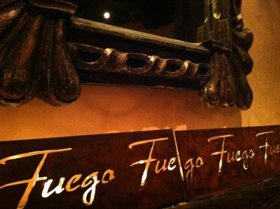 Fuego Restaurant:                                     Fuego metal art with candles lit behind it on a mantle