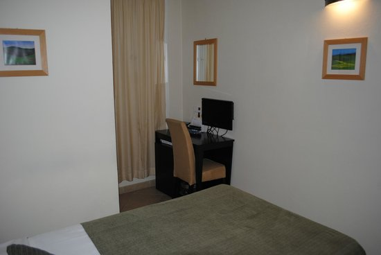 Hotel Globus: Bed and writing desk with small flat-screen TV.