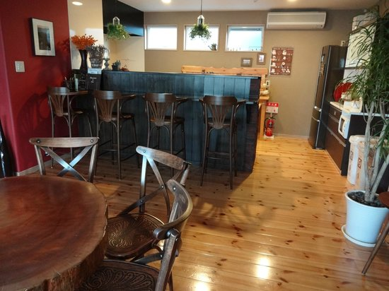 Aso Base Backpackers : from the dinning table looking towards the bar w/stools that separates the kitchen