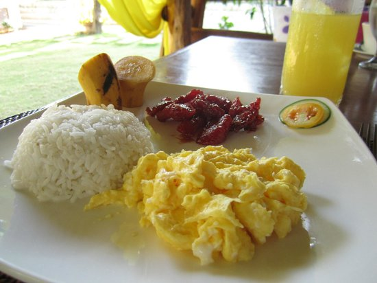 Breakfast. Scrambled eggs, tocino, rice, fruits and juice