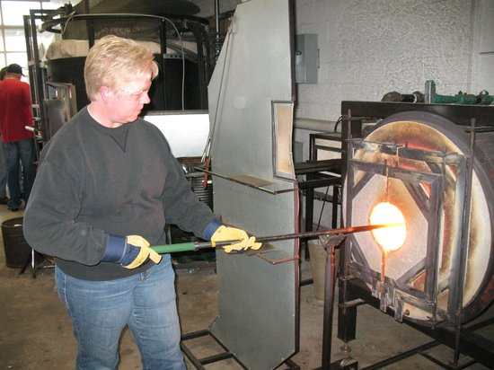 Tacoma Glassblowing Studio: Putting pipe into glory hole to heat.