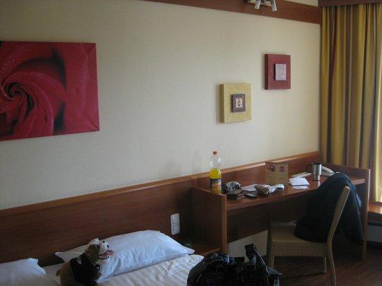 Star Inn Hotel Regensburg : Bett mit Arbeitsbereich