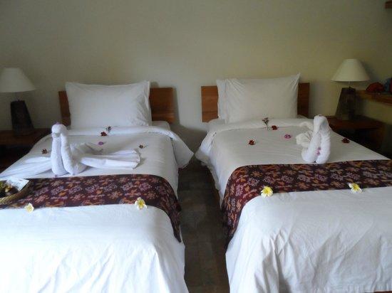 Sri Ratih Cottages: pliage des serviettes sur nos lits parsemès de fleurs