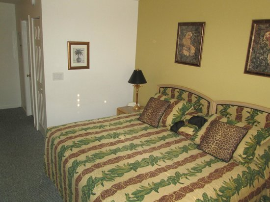 The Cozy Inn: View of King bed with bathroom hall in background