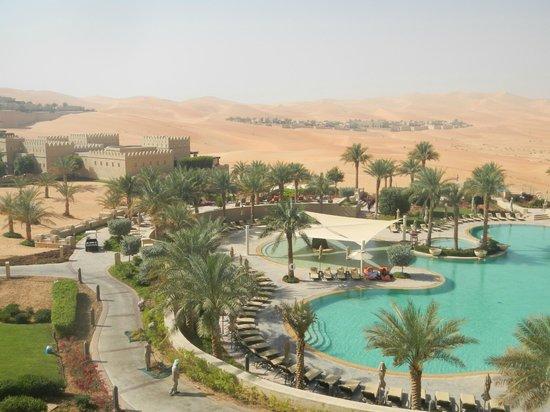 Qasr Al Sarab Desert Resort by Anantara: Pool and Desert background beyond oasis