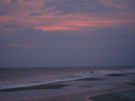 St. James Plantation: Beautiful sunset behind storm clouds at beach clubhouse