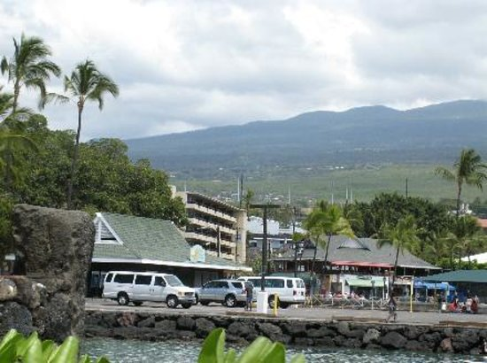 Kona Seaside Hotel : the view from the harbor, with mountains in distance, hotel at left center of photo