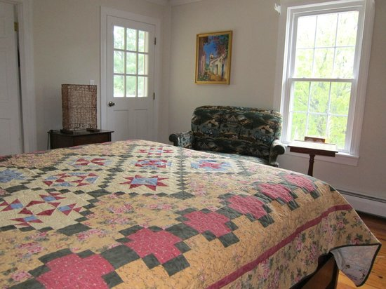 Shenandoah Manor Bed and Breakfast: View of quilt on bed and loveseat in room.  Door leads to outdoor balcony to relax outside.