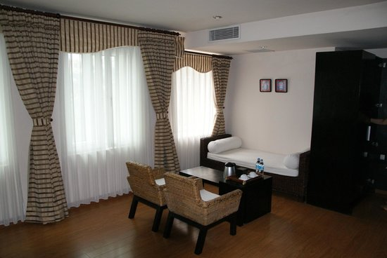 โรงแรมเอนีส: Spacious lounge and coffee table with three massive windows providing bright airy feel to room