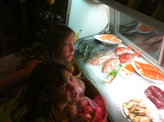 Girls trying to copy fish faces in the food display case for Ponte vedra fish camp