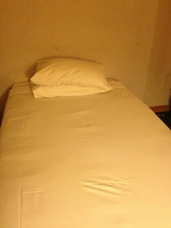Ramal Hotel Kuwait: A bed without a headboard ! and unorganized sheets.